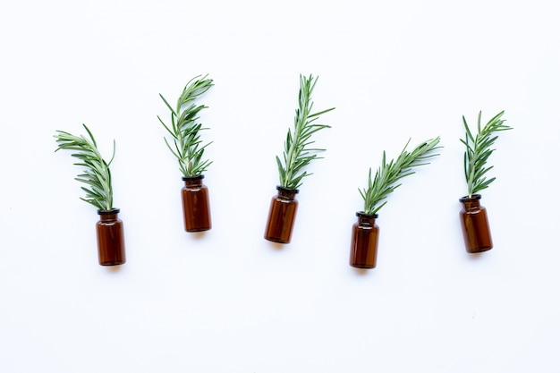 Bottle of essential oil with rosemary on white