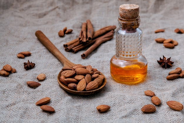Bottle of extra virgin almonds oil with whole almonds.