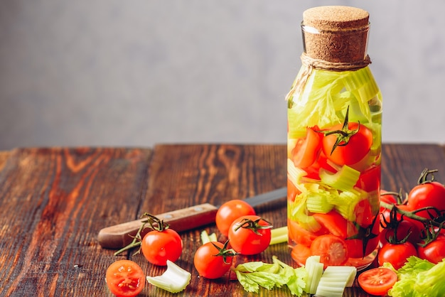 Bottle of flavored water with vegetables cherry tomato and celery stems