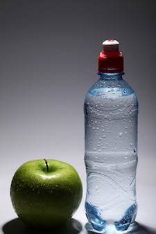 Bottle of fresh cold water and green apple