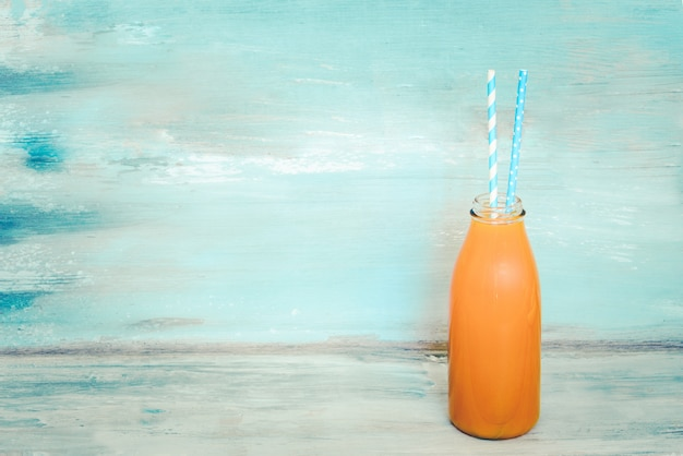 A bottle of fresh juice with two straws in front of a blue rustic background. copy space, mock-up.