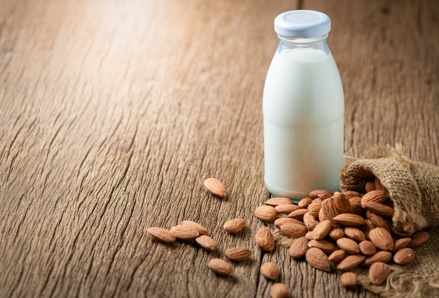 Bottle of fresh milk and almonds on wooden table
