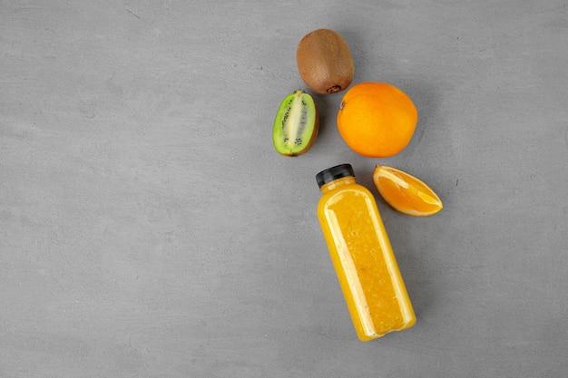 Bottle of freshly squeezed orange juice on gray surface