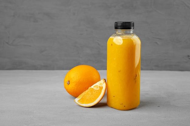 Bottle of freshly squeezed orange juice on gray