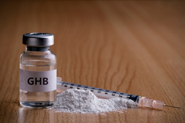 Bottle of ghb with drug powder and injection needle on wooden surface  ghb