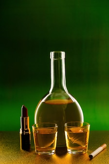 A bottle and a glass of alcohol and cigarettes