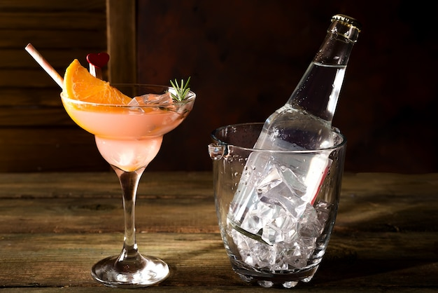 Bottle and a glass of alcohol cocktail with ice and orange on a dark wooden background