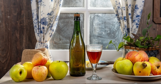 Bottle and glass of cider with apples. near the window, in rustic house