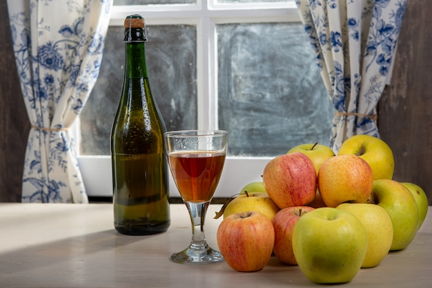 Bottle and glass of cider with apples. near the window, in the rustic house