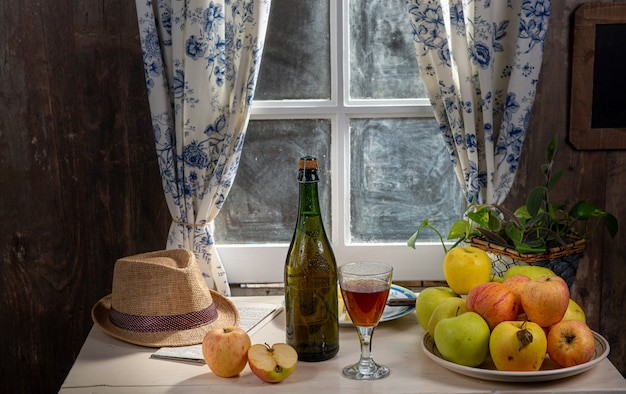Bottle and glass of cider with apples. in rustic house