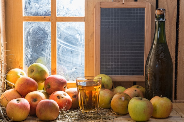 Bottle and glass of cider with apples