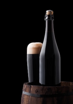 Bottle an glass of craft dark stout beer on wooden barrel on black background