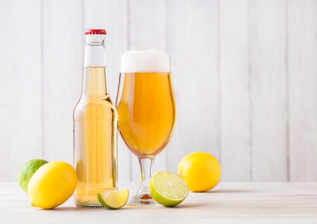 Bottle and glass of lager beer with lemon and lime on light wooden background