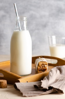 A bottle and a glass of milk with cereal bars on a wooden tray with a brown napkin