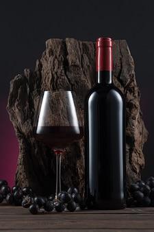 Бутылка, бокал испанского красного вина и виноград на деревянной основе