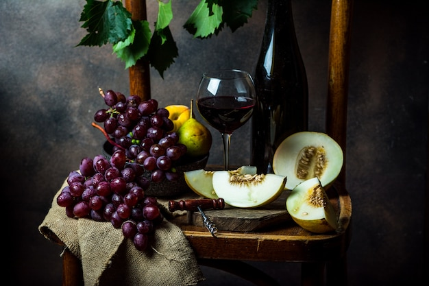 Bottle and glass of red wine, grape and cork on chair. melon, piece of melon. pink grape, pear. still life of food. dark food photography. autumn concept. alcohol, viticulture.