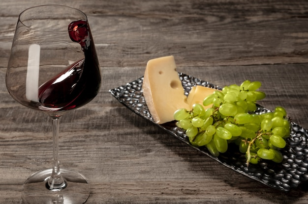 Una bottiglia e un bicchiere di vino rosso con frutta su legno