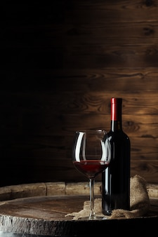 Bottle and glass of red wine on wooden barrel shot with dark wooden background