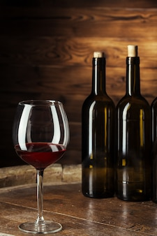 Bottle and glass of red wine on wooden barrel shot with dark wooden