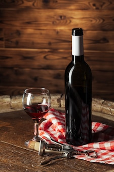 Bottle and glass of red wine on wooden barrel shot