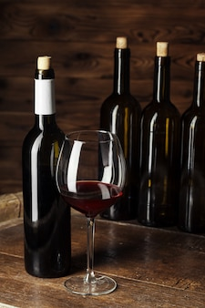 Bottle and glass of red wine on wooden barrel  with dark wooden