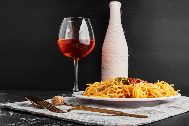 A bottle and glass of rose wine with spaghetti.