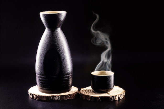 Bottle and glass of sake, hot japanese alcoholic drink, with steam, black background and copy space