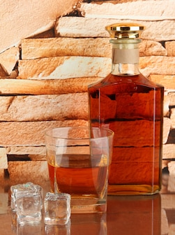 Bottle and glass of whiskey and ice on brick wall