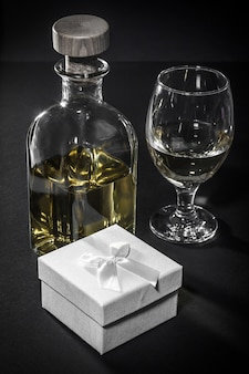Bottle and glass of white wine, gift box on black background. valentine's day greeting card concept.