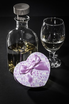 Bottle and glass of white wine, gift box in shape of a heart on black background. valentine's day greeting card concept.