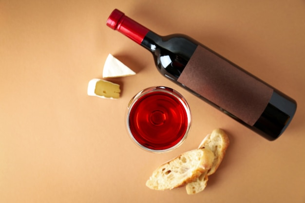 Bottle and glass of wine, cheese and bread on beige background