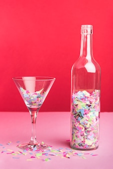 Bottle and glass with colorful confetti