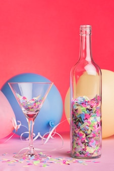Bottiglia e bicchiere con coriandoli su sfondo rosso