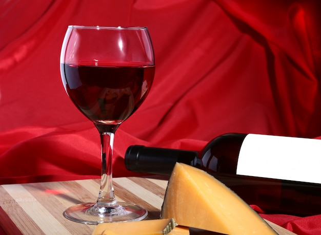 Bottle and glass with red wine grapes and chees on wooden table.