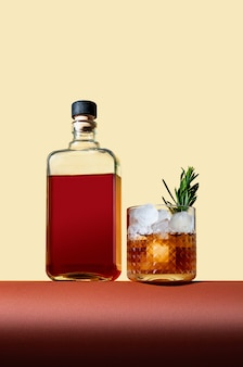 Bottle and glass with whiskey and ice on brown table on light background. modern style. creative concept