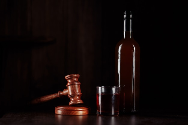 Bottle and glass with whisky and judge gavel, alcohol and crimes concept.