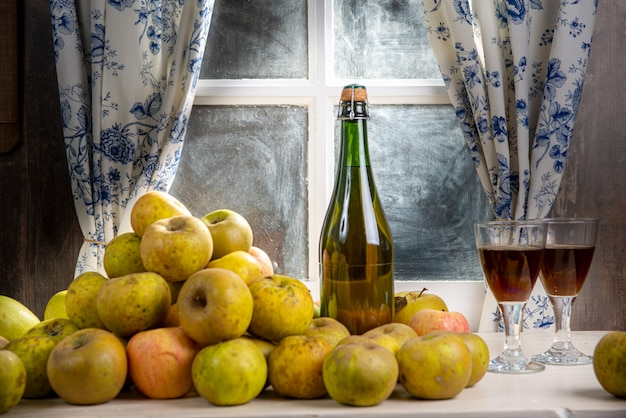 Bottle and glasses of cider with apples, near the window, in rustic house