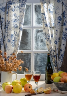 Bottle and glasses of cider with apples. in rustic house, window background