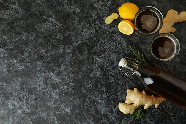 Bottle and glasses of ginger beer and ingredients on black smoky