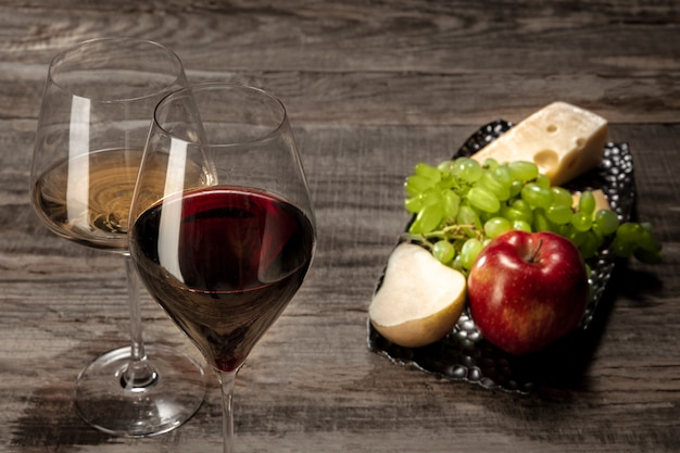 A bottle and glasses of red and white wine with fruits
