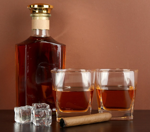 Bottle and glasses of whiskey and ice on brown surface
