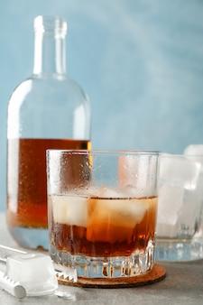 Бутылка, бокалы с кубиками льда и виски на сером фоне, крупный план