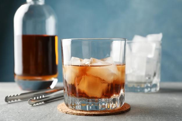 Бутылка, бокалы с кубиками льда и виски на сером