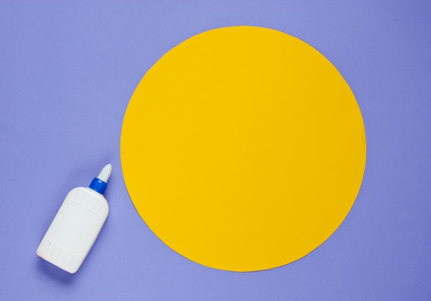 Bottle of glue on a purple paper with a circle
