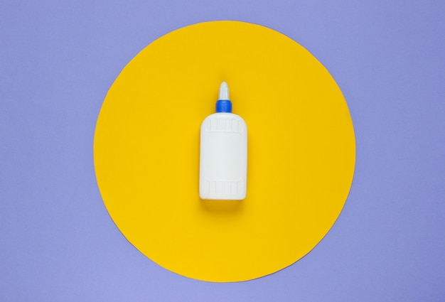 Bottle of glue on a purple paper with yellow circle