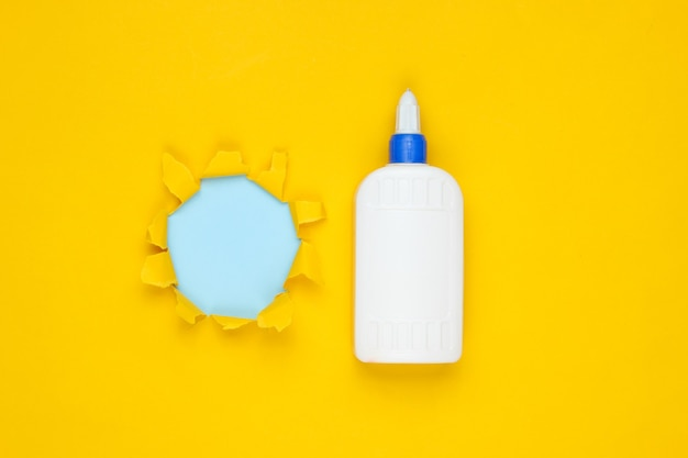 Bottle of glue on yellow paper with torn hole