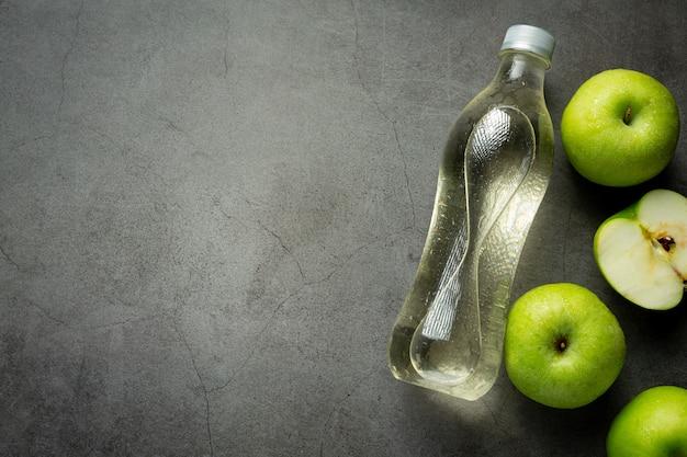 Una bottiglia di succo di mela verde sano messo accanto a mele verdi fresche