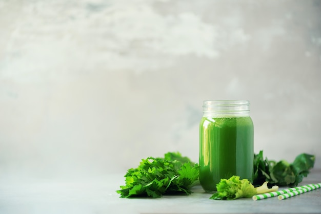Bottle of green celery smoothie on grey concrete background