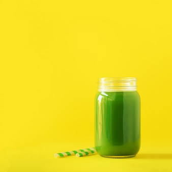 Bottle of green celery smoothie on yellow background
