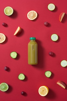 Bottle of green fruit and vegetable juice in the center of the image surrounded by pieces of various colored fruits and vegetables on a red background